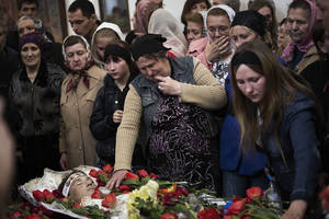 Photo - The mother of Sigarov Alexander, 24, reaches for his body at a church during the funeral for three people killed last Sunday in a shooting by unknown gunmen at a checkpoint, in Slovyansk, Ukraine, Tuesday, April 22, 2014. (AP Photo/Manu Brabo)