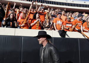 Photo - Trace Adkins walks on the field before a college football game between the Oklahoma State University Cowboys (OSU) and the University of Kansas Jayhawks (KU) at Boone Pickens Stadium in Stillwater, Okla., Saturday, Nov. 9, 2013. Photo by Sarah Phipps, The Oklahoman