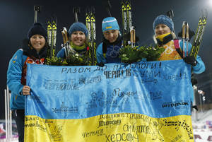 Photo - FILE - In this Friday, Feb. 21, 2014, file photo Ukraine's relay team Vita Semerenko, Juliya Dzhyma, Olena Pidhrushna and Valj Semerenko, from left, celebrate with a Ukrainian flag with writings on it after winning the gold during the women's biathlon 4x6k relay, at the 2014 Winter Olympics in Krasnaya Polyana, Russia. With the crisis in Ukraine escalating by the day, the prospect of holding the Winter Olympics in the former Soviet republic seems hard to imagine. Yet, the western Ukrainian city of Lviv hasn't given up on its bid for the 2022 Games. Lviv remains among the five contenders in what is turning into a very unstable race, vying with Almaty, Kazakhstan; Beijing; Krakow, Poland; and Oslo. (AP Photo/Dmitry Lovetsky, File)