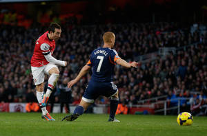 Photo - Arsenal's Santi Cazorla, left, scores his side's second goal past Fulham's Steve Sidwell during the English Premier League soccer match between Arsenal and Fulham at the Emirates Stadium in London, Saturday, Jan. 18, 2014.  (AP Photo/Matt Dunham)