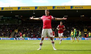 Photo - Arsenal's Aaron Ramsey celebrates scoring the first goal of the game during their English Premier League soccer match against Norwich City at Carrow Road, Norwich, England, Sunday, May 11, 2014. (AP Photo/PA Wire)    UNITED KINGDOM OUT    -   NO SALES    -   NO ARCHIVES