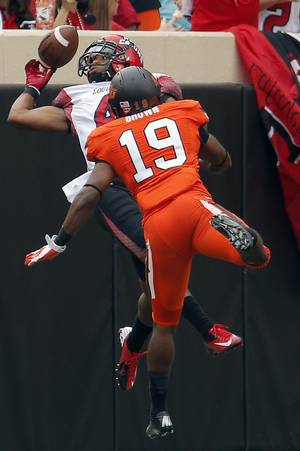 photo - Oklahoma State's Brodrick Brown (19) breaks up a pass intended for Louisiana-Lafayette's Javone Lawson (4) during a college football game between Oklahoma State University (OSU) and the University of Louisiana-Lafayette (ULL) at Boone Pickens Stadium in Stillwater, Okla., Saturday, Sept. 15, 2012. Photo by Sarah Phipps, The Oklahoman