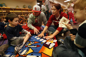 Photo - Baseball pitcher Cole Stevens, wearing a cap, and rowing athlete Ashley Lafollette use playing cards to teach math skills to Luca Perillo, 6, left, and Ryan Floyd, 6.  PHOTOS BY STEVE SISNEY, THE OKLAHOMAN