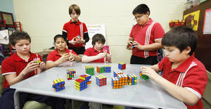 Photo - Members of the GT Rubik's Cube Club at Dove Science Academy Elementary School solve various types of cubes. They are, from left, fifth graders Nicholas Nieman, 10; Jose Calderon, 11; William Mlekush, 11; Dustin McWilliams, 11; Emanuel Carrizales, 11; and fourth grader Aeneas Freeman, 9.  Photo by Paul B. Southerland, The Oklahoman
