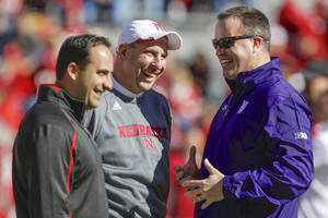 Photo - Northwestern head coach Pat Fitzgerald, right, meets with Nebraska head coach Bo Pelini, center, and Nebraska defensive coordinator John Papuchis, prior to their NCAA college football game in Lincoln, Neb., Saturday, Nov. 2, 2013. (AP Photo/Nati Harnik)