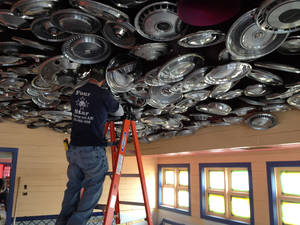 Photo - A construction worker hangs hubcaps from the ceiling in a dining room at the Chuy's restaurant being built at 760 Interstate Drive in Norman. PHOTO PROVIDED