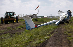 photo -   A tractor is driven away Monday, June 18, 2012, in Wallis, Texas, after a local landowner assisted first responders and National Transportation Safety Board investigators in removing a glider that crashed in a cotton field Sunday, killing three people including a 3-year-old boy. Authorities are trying to determine what led to the crash that happened at about 5 p.m. near the glider facility at Texas 36 and Cougar Drive Sunday evening. Deputies said Fred Blair, 68, of Wallis, and Matilda Blair, 32, and 3-year-old Andrew Blair of Houston died instantly in the crash. The Federal Aviation Administration is expected to investigate the incident, officials said. (AP Photo/Houston Chronicle ,Johnny Hanson)
