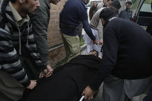 Photo - People carry the body of a police officer into an ambulance in Mardan. Pakistan, Tuesday, Feb. 26, 2013. Police say gunmen have shot dead a police officer protecting a team of polio workers during a U.N.-backed vaccination campaign in northwestern Pakistan. (AP Photo/Sohail Iqbal)