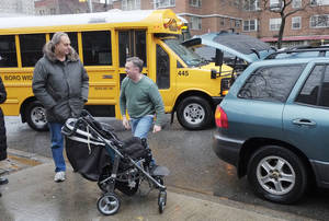 Photo - Peter Curry, center, unloads his daughter's wheel chair from his car after driving her to Public School 33, Wednesday, Jan. 16, 2013 in New York. She would normally be driven by school bus, according to her father. More than 8,000 New York City school bus drivers and aides went on strike over job protection Wednesday morning, leaving some 152,000 students, many disabled, trying to find other ways to get to school. (AP Photo/Mark Lennihan)