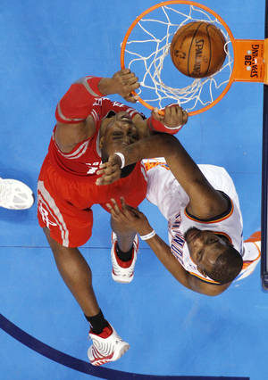 Photo - Houston Rockets center Dwight Howard, left, dunks in front of Oklahoma City Thunder forward Kevin Durant during the third quarter of an NBA basketball game in Oklahoma City, Tuesday, March 11, 2014. Oklahoma City won 106-98. (AP Photo/Sue Ogrocki)