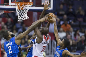 Photo - Washington Wizards forward Chris Singleton, drives to the basket against Orlando Magic forward Kyle O'Quinn, left, forward Andrew Nicholson, center, and forward Maurice Harkless during the first half of an NBA basketball game, Tuesday, Feb. 25, 2014, in Washington. (AP Photo/ Evan Vucci)