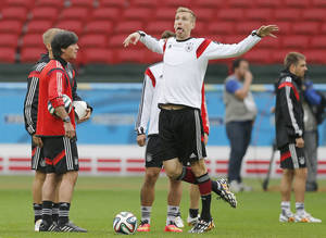 Photo - Germany's Per Mertesacker, center, grimaces to Germany's head coach Joachim Loew, left, during a training session at the Estadio Beira-Rio Stadium in Porto Alegre, Brazil, Sunday, June {try}, 2014.  Germany will play Algeria in a World Cup round of 16 soccer match on June 30. (AP Photo/Frank Augstein)