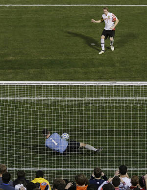 Photo - Georgetown goalie Tomas Gomez blocks the penalty shot of Maryland's Helge Leikvang (6), giving them a win in their NCAA College Cup men's championship semifinal soccer match at Regions Park, Friday, Dec. 7, 2012, in Hoover, Ala. (AP Photo/Dave Martin)