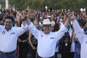 Photo - In this image released by Benjamin Medrano Thursday, July 18, 2013, Benjamin Medrano, center, raises his arms with other unidentified people during a campaign event in Chichimequillas, Mexico, Friday, June 7, 2013. Medrano, the first openly gay mayor ever elected in Mexico, is scheduled to take office in the rough, violence-plagued state of Zacatecas in September. (AP Photo/Courtesy of Benjamin Medrano)