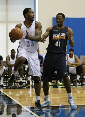 photo - Oklahoma City Thunder's Ryan Reid (33) passes the ball before stepping out of bounds in front of Utah Jazz's Justin Knox (41) during an NBA summer league basketball game, Friday, July 13, 2012, in Orlando, Fla. (AP Photo/John Raoux)  ORG XMIT: DOA103