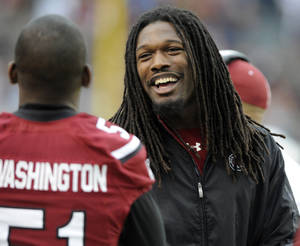 Photo - South Carolina defensive end Jadeveon Clowney, right, talks on the sidelines with teammate Devin Washington (51) during the second half of an NCAA college football game, Saturday, Nov. 23, 2013 in Columbia, S.C. South Carolina beat Coastal Carolina 70-10. (AP Photo/Stephen Morton)