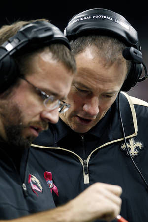 Photo -   New Orleans Saints acting head coach Aaron Kromer, right, goes over plays during an NFL football game against the San Diego Chargers in New Orleans, Sunday, Oct. 7, 2012. (AP Photo/Bill Haber)