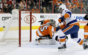 Photo - New York Islanders' Cal Clutterbuck, right, puts the puck in the back of the net past Philadelphia Flyers goalie Steve Mason during the first period of an NHL hockey game, Saturday, Jan. 18,  2014, in Philadelphia. (AP Photo/Tom Mihalek)