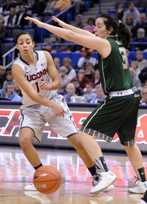 Photo - Connecticut's Bria Hartley, left, is guarded by South Florida's Laura Marcos Canedo (31) during the first half of an NCAA college basketball game in Hartford, Conn., Sunday, Jan. 26, 2014. (AP Photo/Fred Beckham)