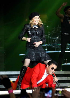 "Photo -   In this Nov. 13, 2012 photo released by Guy Oseary, singer Madonna, left, performs onstage with South Korean rapper PSY during Madonna's MDNA concert at Madison Square Garden in New York. Psy joined the Madonna and her troupe of dancers onstage to perform his hit song ""Gangnam Style"". (AP Photo/Guy Oseary)"