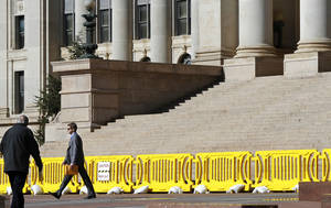 Photo - Bright yellow barriers prevent pedestrians from entering the south plaza area, where debris occasionally falls from crumbling sections of the state Capitol. Photo by Jim Beckel, The Oklahoman