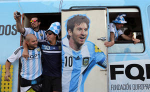 Photo - In this Saturday, June 14, 2014 photo, Argentine fans arrive in a bus decorated with a painting of soccer star Lionel Messi at the Copacabana beach in Rio de Janeiro, Brazil. Waving flags and banners, more than a thousand Argentine fans, many dressed in their team's traditional blue and white, crowded the Copacabana beachfront ahead of Argentina's World Cup match against Bosnia-Herzegovina Sunday in Rio's iconic Maracana stadium. (AP Photo/Leo Correa)
