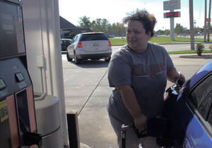 photo - Paula Linares fills her car for $2.99 a gallon at the 7-Eleven at NW12th and Santa Fe in Moore. The average price of gasoline in Oklahoma City has dropped 50 cents over the past month. <strong>Adam Wilmoth - photo by</strong>