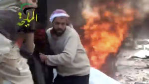 Photo - This citizen journalism image taken from video provided by Shaam News Network, which has been authenticated based on its contents and other AP reporting, shows a wounded man being pulled from the site of a Syrian government airstrike on a gas station in the eastern Damascus suburb of Mleiha, Syria, Wednesday, Jan. 2, 2013. Activists say dozens of people have been killed or wounded in an air raid on a gas station near the capital Damascus. (AP Photo/Shaam News Network via AP video)