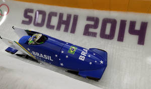 Photo - The team from Brazil BRA-1, piloted by Fabiana Santos, takes a curve during a training run for the women's two-man bobsled at the 2014 Winter Olympics, Friday, Feb. 14, 2014, in Krasnaya Polyana, Russia. (AP Photo/Michael Sohn)