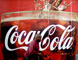 Photo -   FILE- In this Monday, July 16, 2012, photo, a billboard for Coca Cola is seen outside a convenience store in Atlanta. The Coca-Cola Co. says its net income slipped in the second quarter from a year ago, as rising costs for ingredients offset its expansion overseas. The world's biggest beverage maker, which makes Minute Maid, Powerade and Dasani, says revenue growth was powered by higher prices in the U.S. and expansion in emerging markets such as India, where volume rose 20 percent.(AP Photo/David Goldman)