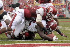 Photo -   Alabama running back Eddie Lacy (42) scores on a 6-yard touchdown run as Arkansas cornerback Kaelon Kelleybrew (23) tried to stop him during first quarter action of an NCAA college football game in Fayetteville, Ark., Saturday, Sept. 15, 2012 (AP Photo/David Quinn)
