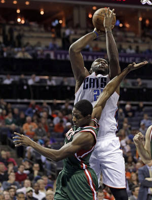 Photo - Charlotte Bobcats' Al Jefferson, back, shoots over Milwaukee Bucks' Brandon Knight, front, during the first half of an NBA basketball game, Monday, Dec. 23, 2013, in Charlotte, N.C. (AP Photo/Chuck Burton)