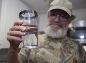 "Photo - Flemington Road community member Sam Malpass of Wilmington, N.C. holds a glass of water from his home on Wednesday, Feb. 19, 2014. Malpass and his wife Pat are part of a small community near L.V. Sutton Complex operated by Duke Energy they feel could be polluting well water with spill off and seepage from large coal ash ponds. ""If you want to know what it's like living near a coal ash pond, this is it,"" said Malpass, 67, a retired carpenter and Vietnam veteran. ""We're afraid to drink the water because we don't know what's in it. We can't eat the fish because we don't know if it's safe anymore. It's changed our lives out here.""   (AP Photo/Randall Hill)"