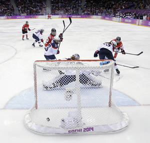 Photo - Marie-Philip Poulin of Canada (29) scores the game-winning goal against USA in overtime during the women's gold medal ice hockey game at the 2014 Winter Olympics, Thursday, Feb. 20, 2014, in Sochi, Russia. (AP Photo/David J. Phillip )