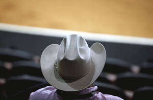 Photo - A cowboy watches the 2010 American Quarter Horse Association World Championship Show reining finals at State Fair Park in Oklahoma City.  Photo by Sarah Phipps, The Oklahoman archives