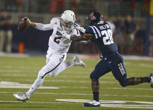 Photo - Texas A&M quarterback Johnny Manziel, left, is tackled by Mississippi defensive back Mike Hilton on Saturday. AP photo