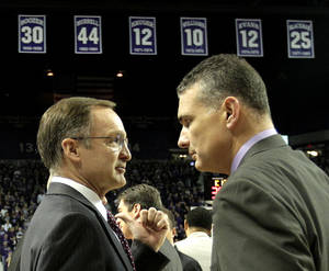 Photo - OU: University of Oklahoma coach Lon Kruger's talks to Kansas State coach Frank Martin as Kruger's number hangs from the rafters at Bramledge Coliseum before an NCAA college basketball game Saturday, Jan. 28, 2012, in Manhattan, Kan. (AP Photo/Charlie Riedel)