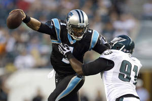 Photo - Carolina Panthers quarterback Cam Newton, left, tries to slip away from Philadelphia Eagles defensive tackle Fletcher Cox during the first half of a preseason NFL football game, Thursday, Aug. 15, 2013, in Philadelphia. (AP Photo/Matt Rourke)