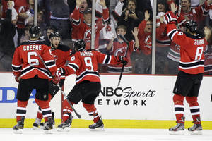 Photo -   New Jersey Devils' Travis Zajac, center left, celebrates with Andy Greene (6), Zach Parise (9) and Dainius Zubrus (8), of Lithuania, after scoring a goal against the New York Rangers the first period of Game 4 of an NHL hockey Stanley Cup Eastern Conference final playoff series, Monday, May 21, 2012, in Newark, N.J. (AP Photo/Julio Cortez)