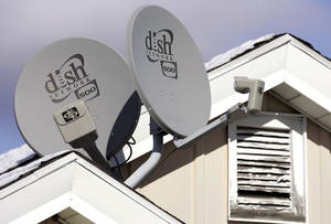 Photo - FILE - In this Nov. 10, 2008 file photo, Dish Network Corp. satellite dishes are attached to a home in Buffalo, N.Y.  Dish Network and Disney have reached a landmark deal Tuesday, March 4, 2014,  that envisions the day when Dish will offer a Netflix-like TV service to people who'd rather stream TV over the Internet than put a satellite receiver on their roof.  (AP Photo/David Duprey, file)