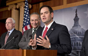 photo - Sen. Marco Rubio, R-Fla., center, takes a reporter's question as a bipartisan group of leading senators announce that they have reached agreement on the principles of sweeping legislation to rewrite the nation's immigration laws, during a news conference at the Capitol in Washington, Monday, Jan. 28, 2013. From left are Sen. John McCain, R-Ariz., Sen. Charles Schumer, D-N.Y., and Sen. Marco Rubio, R-Fla. The deal covers border security, guest workers and employer verification, as well as a path to citizenship for the 11 million illegal immigrants already in this country.  (AP Photo/J. Scott Applewhite)
