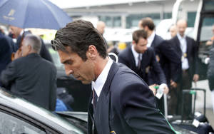 Photo - Italy goalkeeper Gianluigi Buffon carries his luggage upon his arrival with his teammates at Malpensa airport after landing from Brazil, in Milan, Italy, Thursday, June 26, 2014. Italy was disqualified from the World Cup after loosing to Uruguay in their group stage round.  (AP Photo/Luca Bruno)