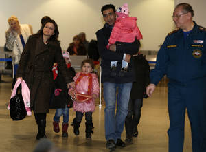 photo - A Russian-Syrian family leave passport control zone just after their arrival from Beirut in Moscow Domodedovo airport , Russia, Wednesday, Jan. 23, 2013. The Kremlin's evacuation of Russians from Syria on Tuesday marks a turning point in its view of the civil war, representing increasing doubts about Bashar Assad's hold on power and a sober understanding that it has to start rescue efforts before it becomes too late. The operation has been relatively small-scale - involving fewer than 100 people, mostly women and children - but it marks the beginning of what could soon turn into a risky and challenging operation.  (AP Photo/Alexander Zemlianichenko)