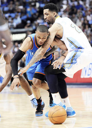Photo - Thunder guard Russell Westbrook loses the ball as he runs into Denver's Wilson Chandler during OKC's loss Monday. AP PHOTO