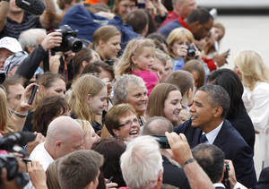 Photo -   President Barack Obama shakes hands with the crowd gathered Friday, Sept. 7, 2012, at the Eastern Iowa Airport in Cedar Rapids, Iowa. (AP Photo/Matthew Putney)