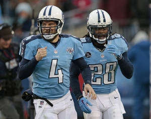 Photo - Tennessee Titans running back Chris Johnson (28) and quarterback Ryan Fitzpatrick (4) head to the sideline after Johnson scored a touchdown against the Arizona Cardinals on a 25-yard pass play in the first quarter of an NFL football game Sunday, Dec. 15, 2013, in Nashville, Tenn. (AP Photo/Wade Payne)