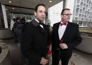 Photo - Nasir Khawaja, left, and Mark Sarver stand outside in line to apply for a marriage license at the Oakland County Clerks office in Pontiac, Mich., Saturday, March 22, 2014. A federal judge has struck down Michigan's ban on gay marriage Friday the latest in a series of decisions overturning similar laws across the U.S. Some counties plan to issue marriage licenses to same-sex couples Saturday, less than 24 hours after a judge overturned Michigan's ban on gay marriage. (AP Photo/Paul Sancya)