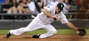 Photo -   Chicago White Sox third baseman Kevin Youkilis attempts to stop a single hit by Minnesota Twins' Jamey Carrol in the second inning of their baseball game in Chicago, Monday, Sept. 3, 2012. (AP Photo/Paul Beaty