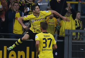 Photo - Dortmund's Robert Lewandowski of Poland, top, celebrates after scoring during the German first division Bundesliga soccer match between BvB Borussia Dortmund  and SC Freiburg in Dortmund, Germany, Saturday, Sept. 28, 2013. (AP Photo/Frank Augstein)