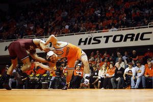 Photo - Oklahoma's 149-pound wrestler Kendric Maple and Oklahoma State's Josh Kendig grapple for position during a wrestling dual between Oklahoma State and Oklahoma at Gallagher Iba Arena in Stillwater on Feb. 9, 2014. Photo by KT King/For the Oklahoman